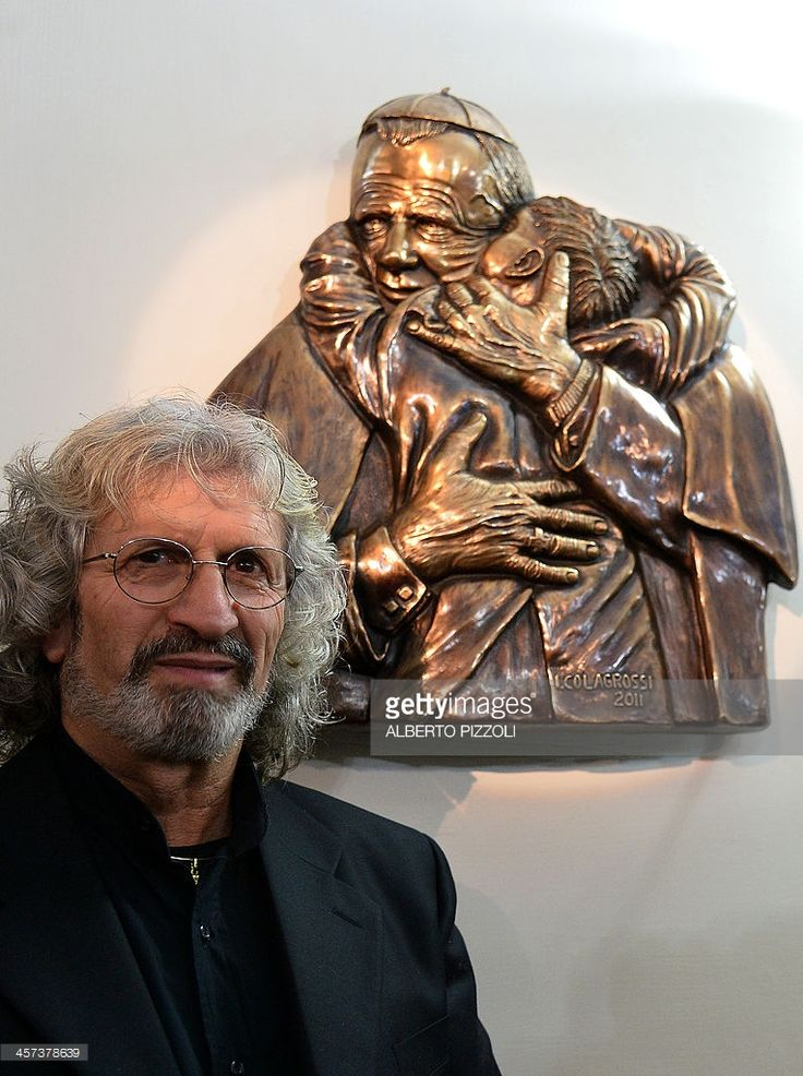 Italian artist Ignazio Colagrossi poses next to a copy of his sculpture showing John Paul II embracing a child on December 17, 2013 at the Vatican.