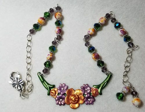 American made brass floral swag - painted with specialty paints.  Neckpiece is Czech glass and Sterling Silver.