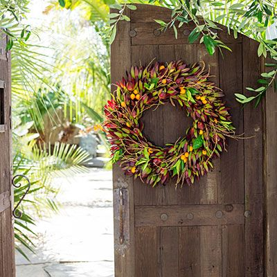 Clusters of yellow-orange kumquats and a few green citrus leaves add contrast to a red Leucadendron base. Dried palm stems provide a dash of orange. The colors are evocative of Christmas without being too Christmas-y.
