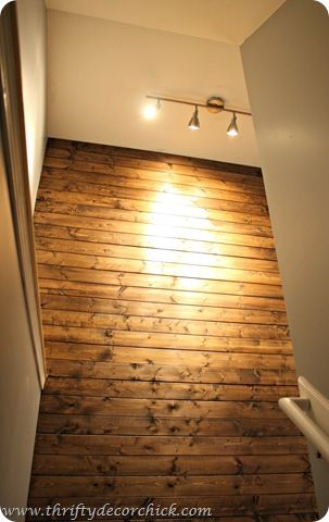 Create this wall in stairway w/ 1x6's or plank wood + dark walnut stain.  DIY cost apprx $50.00  Thrifty Decor Chick: DIY wood planked wall