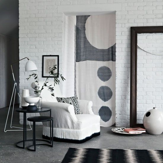 Black and white living room with curtain panel.