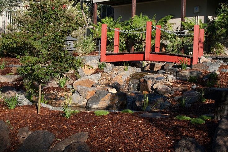 Arched timber bridge over the stream. Painted red to suit the oriental theme of the garden. The stream runs into a set of waterfalls immediately after the bridge.