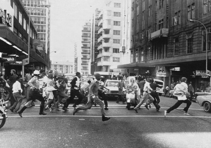 Black youths race through the streets of Johannesburg, South Africa on Thursday, Sept. 23, 1976, fleeing police who fired shots to break up demonstrations against the government by roving mobs.