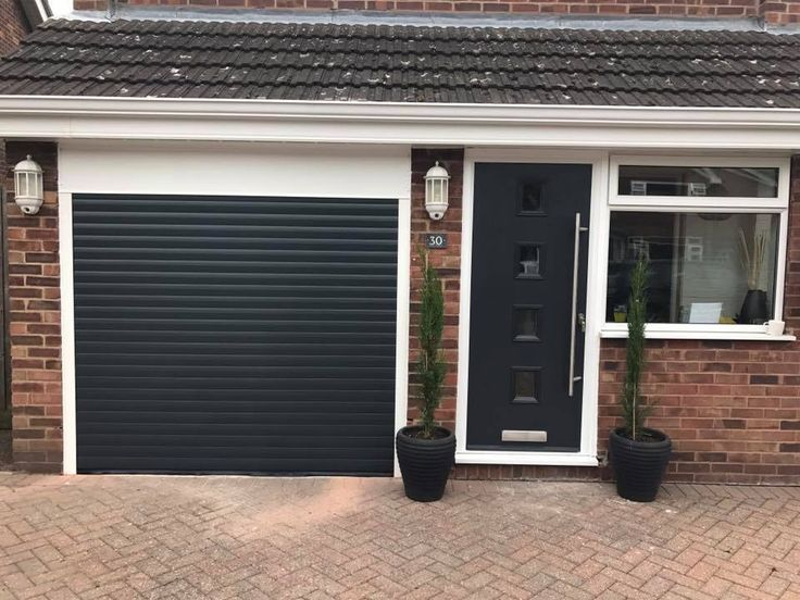 Anthracite grey insulated and remote control roller garage door and matching Door-Stop composite front door long bar handle fitted in Sapcote