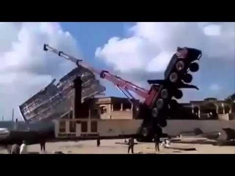 Construction fail. A massive crane helped by an axcavator failed in moun...