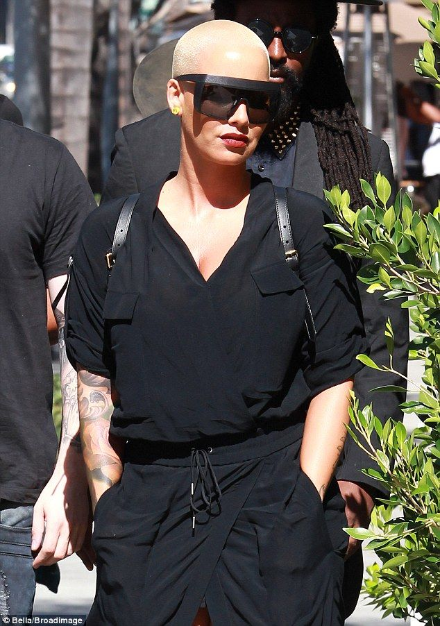Turning heads: The 31-year-old model wore a black shirt dress as she was accompanied by her entourage