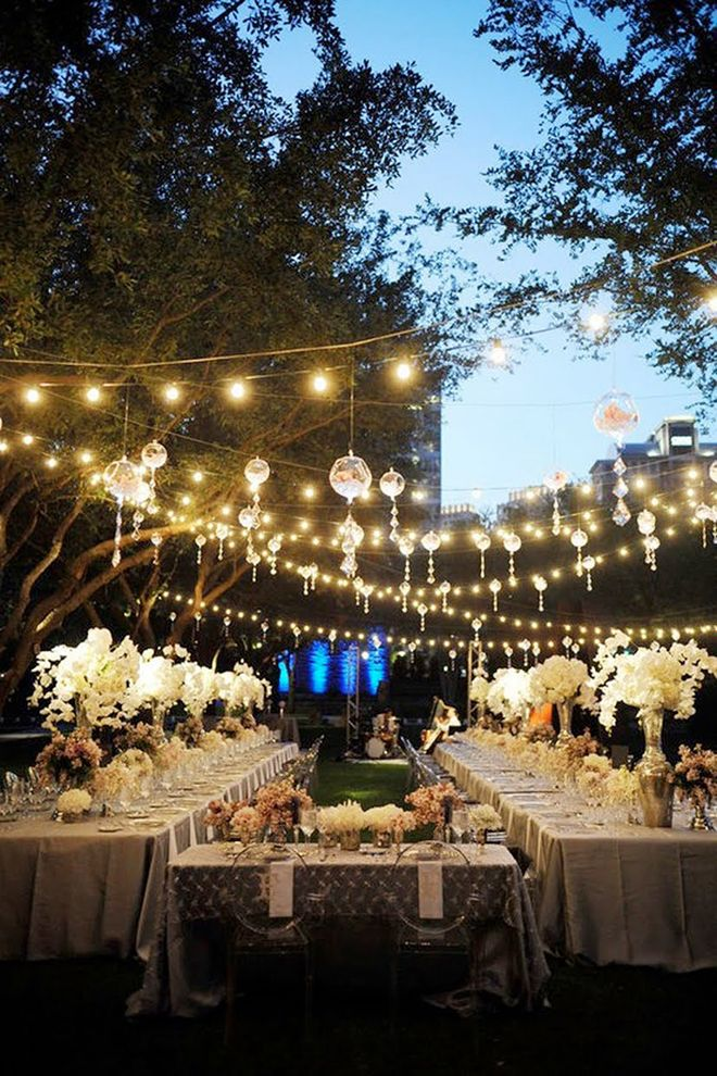 Garden Reception + Long Tables entertains outdoors like the u shaped table arrangement and the lights strung overhead, and glass baubles with flowers