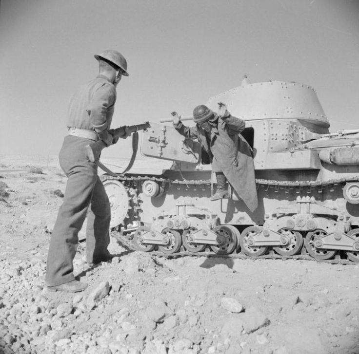 A member of the crew of an Italian M13/40 tank giving himself up near Gazala. His captor might be a soldier of the Polish Independent Carpathian Rifles Brigade. 1941-12-22