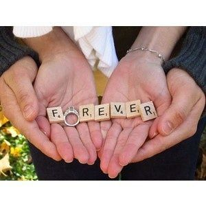 Wedding bride and grooms hands with forever spelled out with scrabble tiles and the brides ring