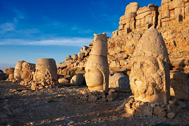 Pictures of the statues of around the tomb of Commagene King Antochus 1 on the top of Mount Nemrut, Turkey . In 62 BC, King Antiochus I Theos of Commagene built on the mountain top a tomb-sanctuary flanked by huge statues (8–9 m/26–30 ft high) of himself, two lions, two eagles and various Greek, Armenian, and Iranian gods. The photos show the broken statues on the  2,134 m (7,001 ft)  mountain. 1
