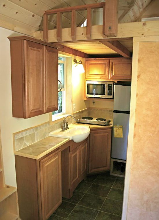 Closer view of the kitchen. Has everything you'd need. Not crazy about bathroom-type sink. I'd like built in 2 burner and tiny oven, not microwave. Plus side--Countertop & floors look like they have been done cheaper than in most tiny houses. Good to see options. 24' Tiny house on wheels.
