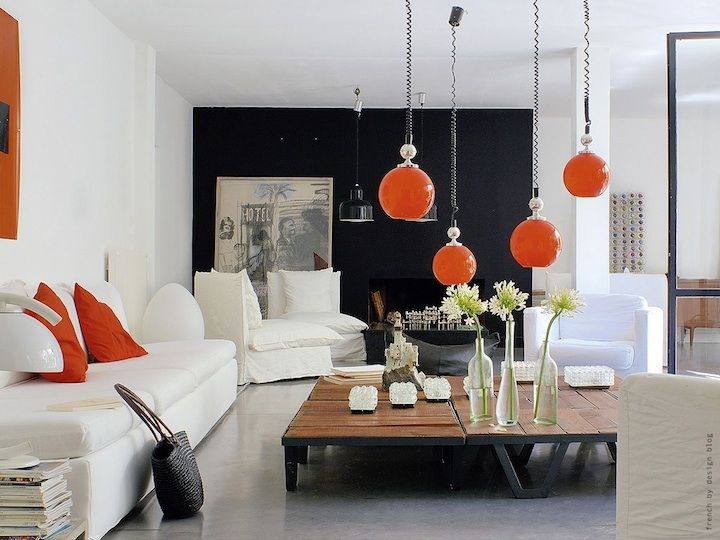 Room With White Walls And A Black Accent Wall Has Pops Of Orange Accents