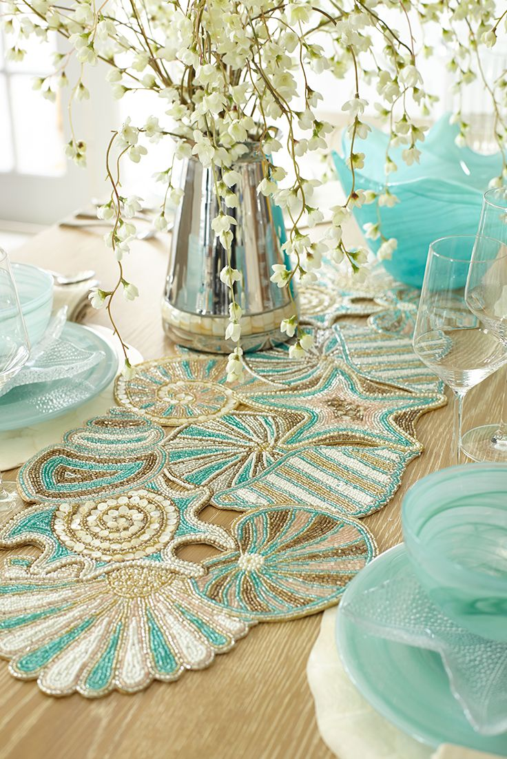 Bring the beach to the table without trailing in salt and sand. With its cool hues of almond, salmon and sapphire beaded to resemble button, clam and ladder horn shells, Pier 1's Beaded Shells Table Runner makes the perfect accompaniment to your next post-swim meal.