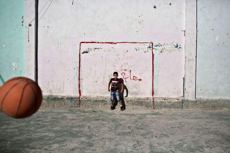 A Palestinian boys uses a basketball to play soccer in the West Bank refugee camp of Jalazoun on June 13. (Muhammed Muheisen/Associated Pres...