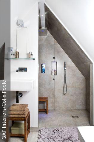 Der Raum mit steilen Dachschrägen fungiert als Bad. Die ebenerdige Dusche ist ausgestattet mit grauen Fliesen in Steinoptik und einem Regenduschkopf. Ein fliederfarbener Langflorteppich sorgt für eine warme Atmosphäre.