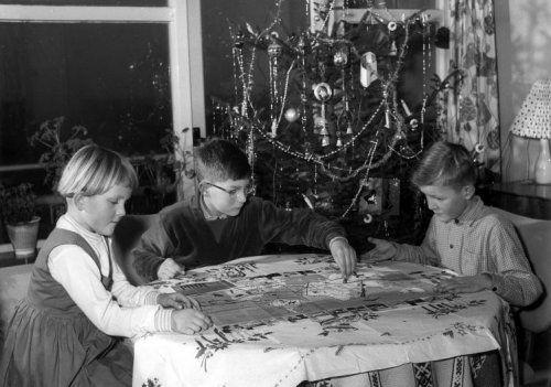 Drie kinderen aan tafel onder de kerstboom, bezig met het spelen van een bordspel. Plaats en jaartal onbekend.