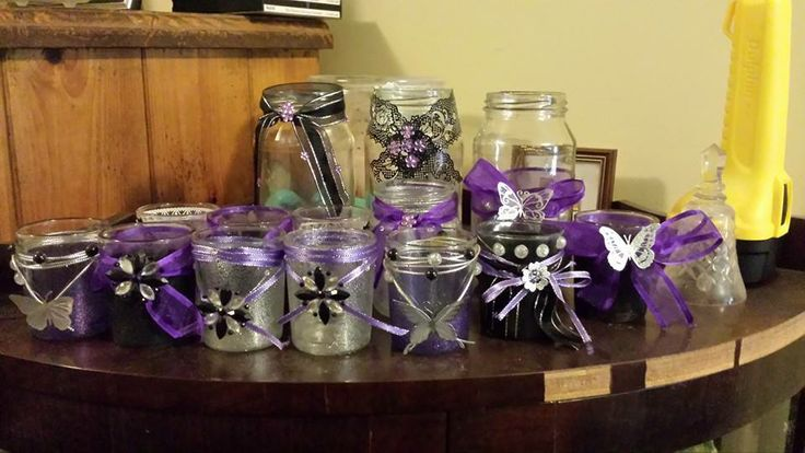 Jars and cheap glass votive holders decorated for my daughter's 18th birthday party. Colour scheme is black, purple and silver. I used an assortment of decoration methods. Some are done with spray on glitter, others were PVA and glitter,