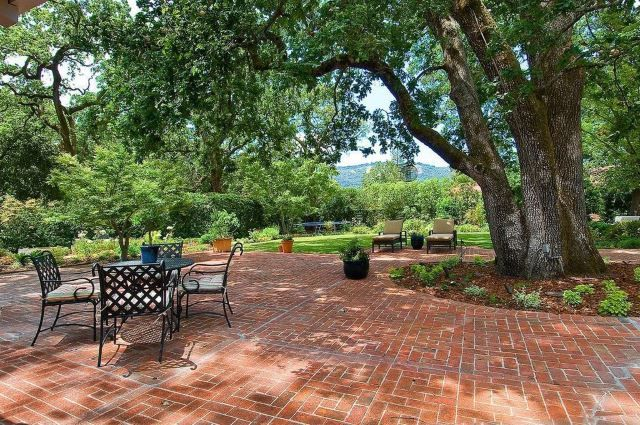 This large expanse features a traditional red brick patio with white grout. This was the customary patio you'd find in all kinds of homes across the country and still looks super great today. This is a relatively large patio design, but this kind of look can be executed in all types of outdoor areas. The trees in the photo provide lots of useful shade so the use of a gazebo or covered are isn't' necessary. You could, of course, still incorporate that into the mix if that's what you prefer.