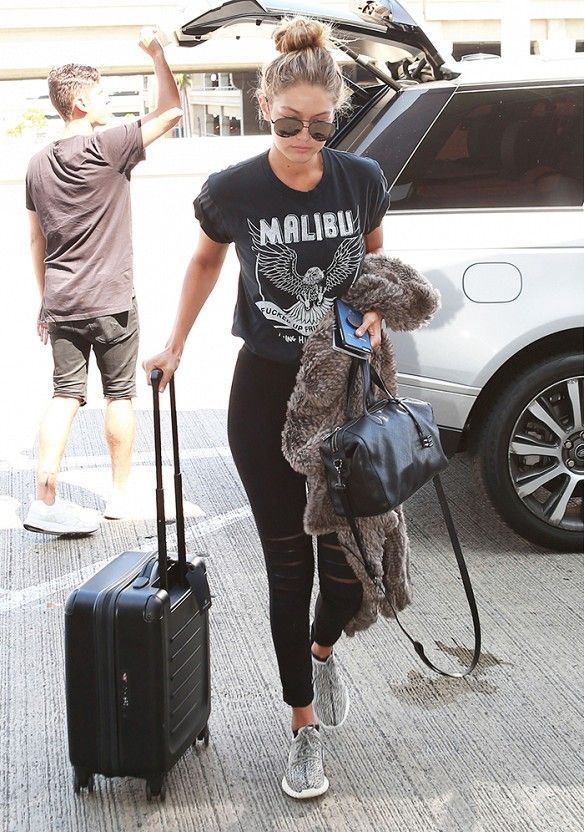 Gigi Hadid wears a graphic crop tee with black distressed skinny jeans, grey tennis shoes, a black bag and sunglasses.