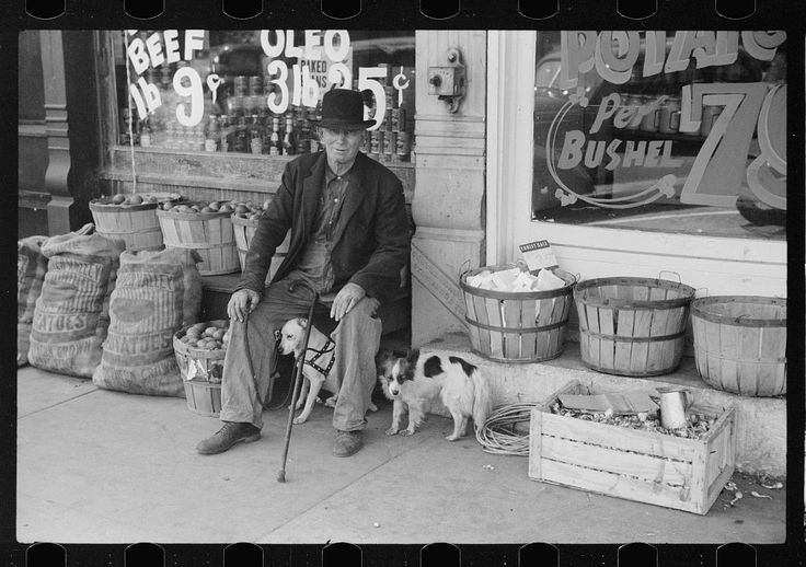 Man and dogs in front of grocery store, Robinson, Illinois. FSA photographer John Vachon, May 1940