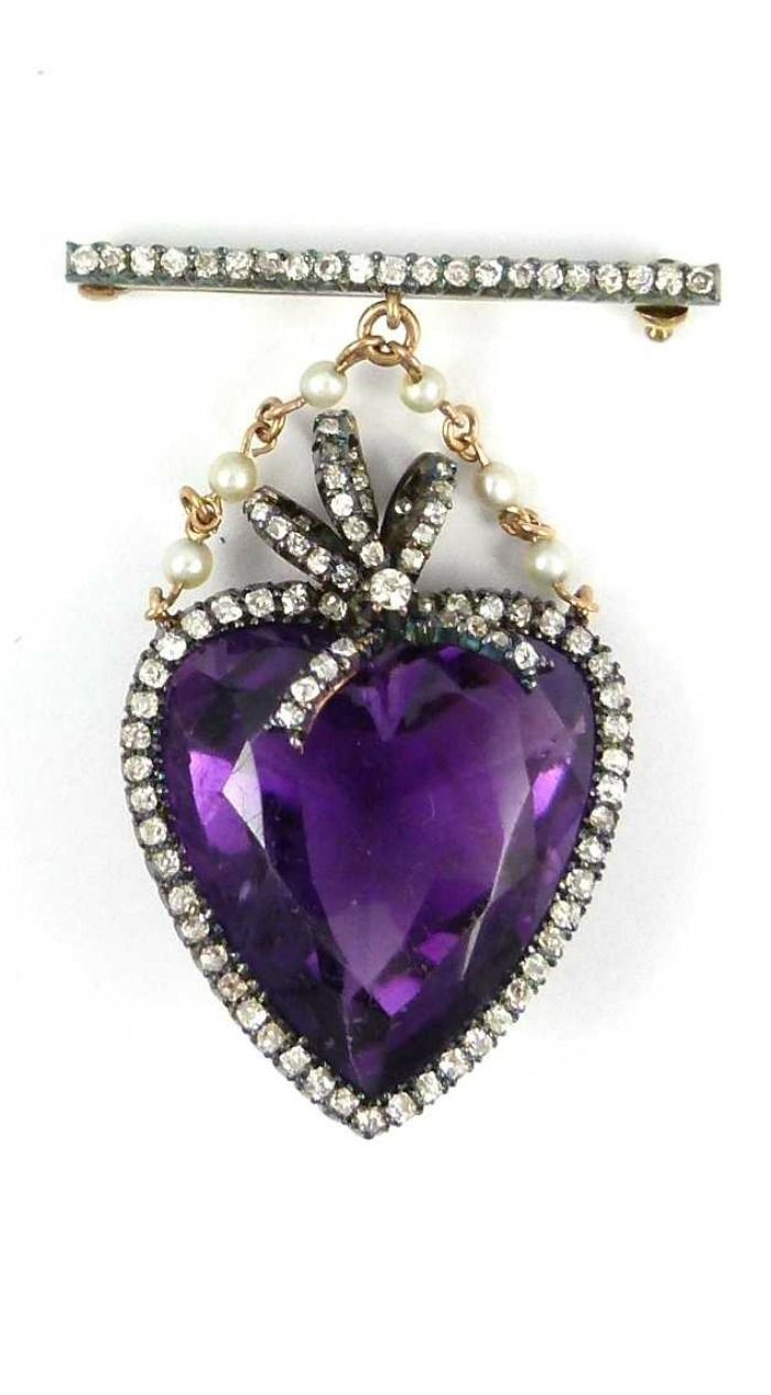 Early 20th century heart shaped amethyst and diamond set brooch, c.1905, the facetted amethyst heart bordered by diamonds and with triple loop diamond surmount, hung on a twin seed pearl and gold chains from a diamond line bar brooch, mounted in silver and gold. At SJ Phillips.