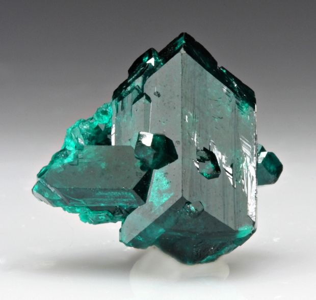 Dioptase ~ Late in the 18th century, copper miners at the Altyn-Tyube (Altyn-Tube) mine, Karagandy Province, Kazakhstan thought they found the emerald deposit of their dreams. They found fantastic cavities in quartz veins in a limestone, filled with thousands of lustrous emerald-green transparent crystals. The crystals were dispatched to Moscow, Russia for analysis. However the mineral's inferior hardness of 5 compared with emerald's greater hardness of 8 easily distinguished it. Later Fr…
