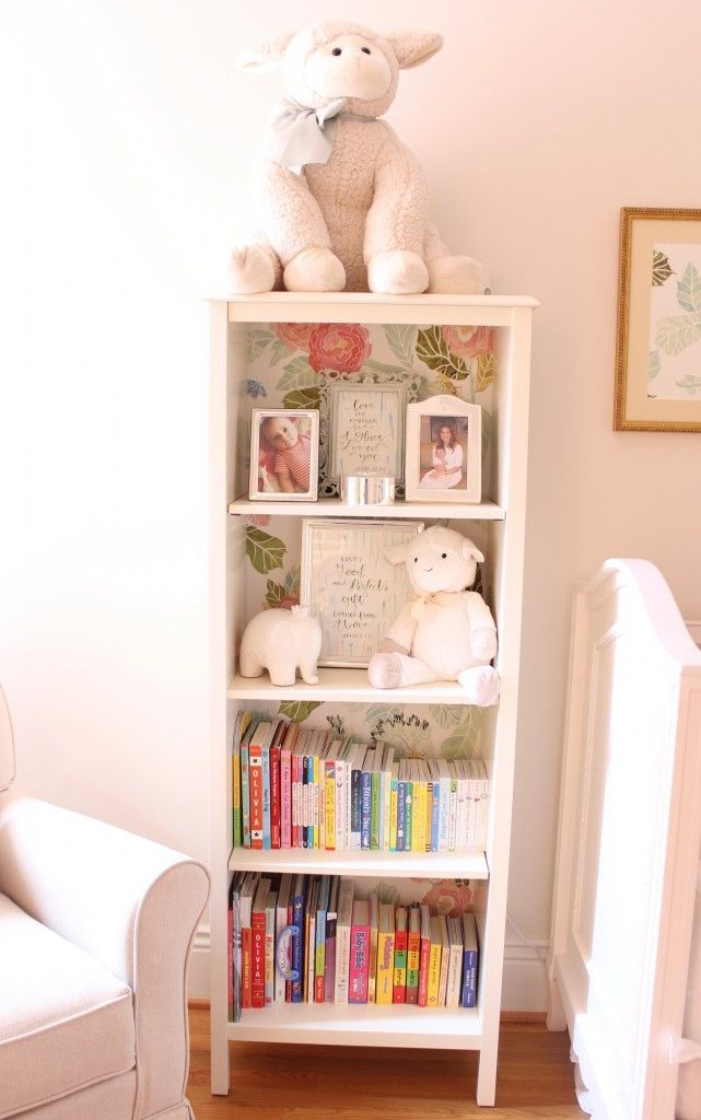 White bookshelf lined with Anthropologie floral wallpaper in this vintage inspired baby girl's room.