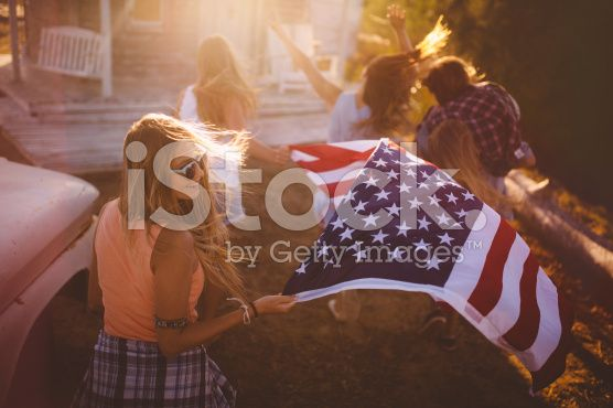 Teen friends carrying an American flag outside royalty-free stock photo