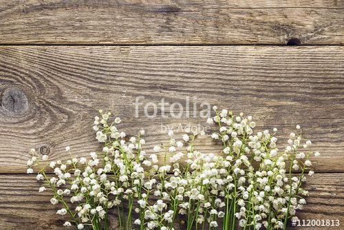 Flowers of lily of the valley on the old wooden background. Plac