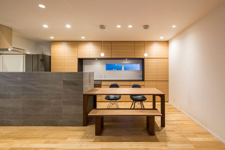 リビングからキッチン・ダイニングを見る:タモの床や壁面収納と、キッチンを囲む石貼りの対比が印象的