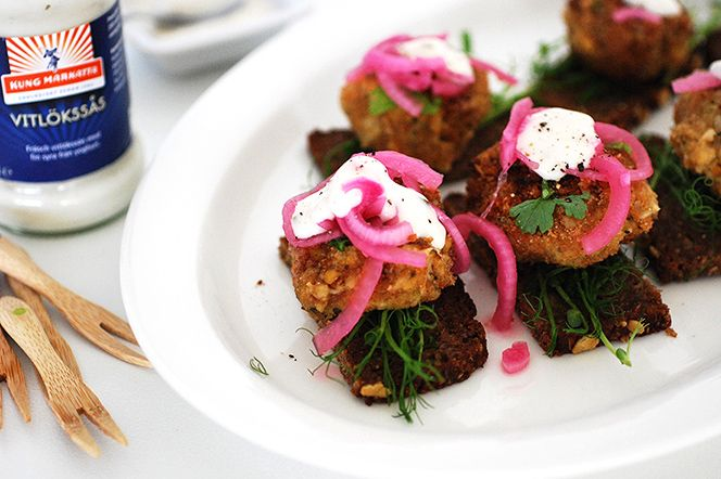 Dessa falafeltapas serveras på rågbröd och toppas med picklad rödlök och vitlökssås. Fantastiskt goda tapas som passar bra som förrätt, på en buffé eller som ett matigt drinktilltugg.