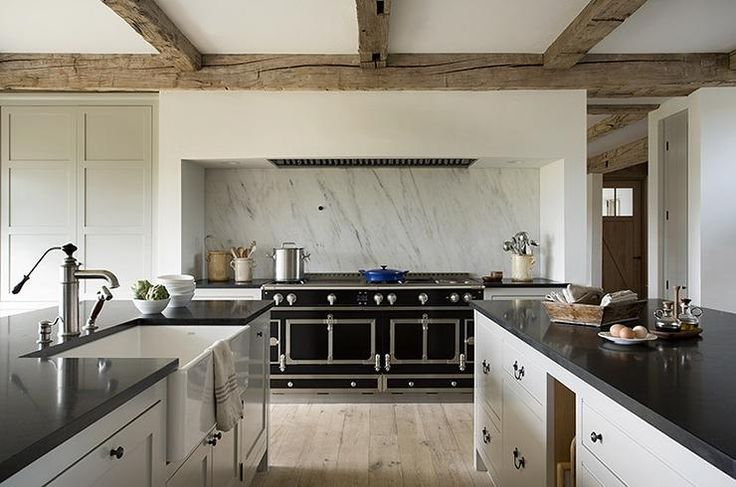 European kitchen features rustic wood ceiling beams over a cooking nook filled with a black La Cornue CornuFe Range under a marble slab backsplash.