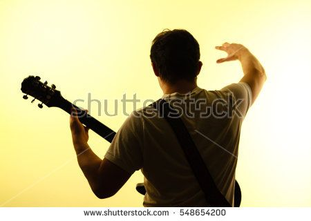 Guitarist waving from behind. adult, back, black, concert, electric, guitar, guitarist, heavy, man, metal, music, musician, playing, rock, short hair, strings, studio, white, yellow, young