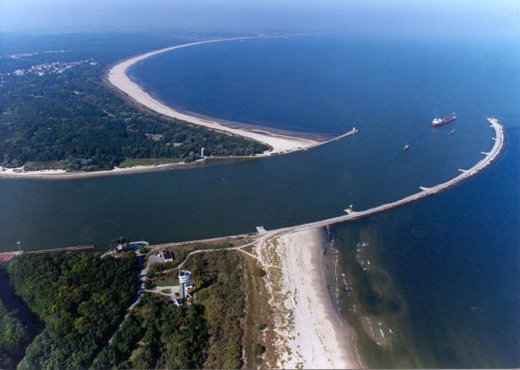 "The river mouth of Świna at the Baltic Sea, separating the islands of Usedom (in the background) and Wolin (in the foreground). The city's name translates as ""Swinamouth"" both in Polish and German, akin to Dartmouth or Plymouth in English"