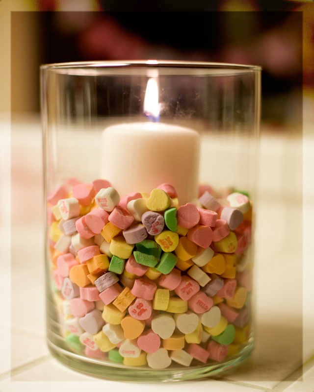 Candy hearts as vase filler for Valentine's Day.  Could use a pink candle to create a pink pastel Valentine celebration for my granddaughter (who's coming out of her purple stage and heading into pink).