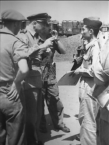 Overdracht materiaal. Te Soerabaja werd aan de Kalimasweg een aanzienlijke hoeveelheid rollend materiaal aan de Kapitein Sriamin van de TNI LMD overgedragen. Aanwezig waren de Ned. Tpn. Cdt. O-Java, Generaal Majoor Scheffelaar en de Terr. Tpn. Cdt. TNI O-Java, kolonel Sungkono. Generaal Scheffelaar in gesprek met Kapitein Sriamin van de TNI LMD.   1950-03-24 (Collectie Indisch Herinneringscentrum)