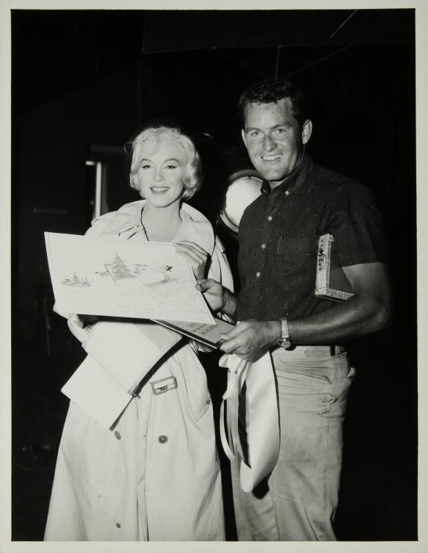 Marilyn on the set of Let's Make Love receiving a card from the cast and crew.