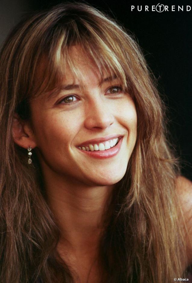 PHOTOS – En 1998, Sophie Marceau laisse sa frange naturelle. Un peu longue, elle cache ses sourcils et se pare de mèches blondes très tendance dans les 90's.