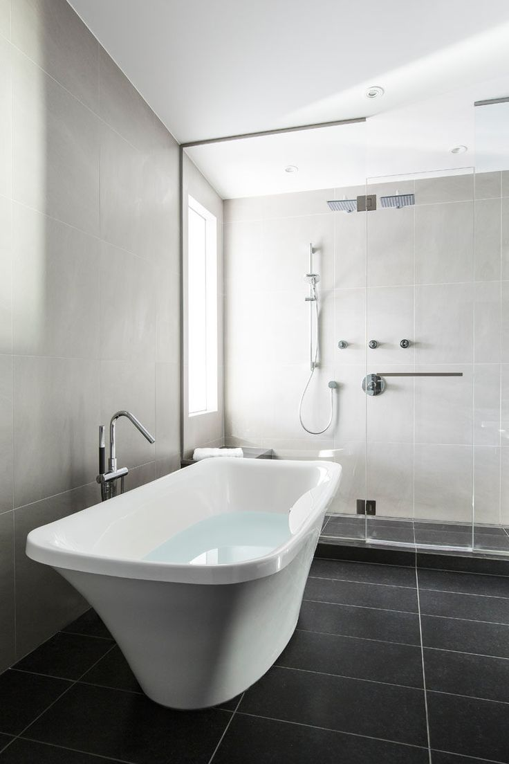 In this master bathroom, light grey tiles cover the walls, while charcoal tiles cover the floors. A glass shower surround allows the light from the window to fill the bathroom.