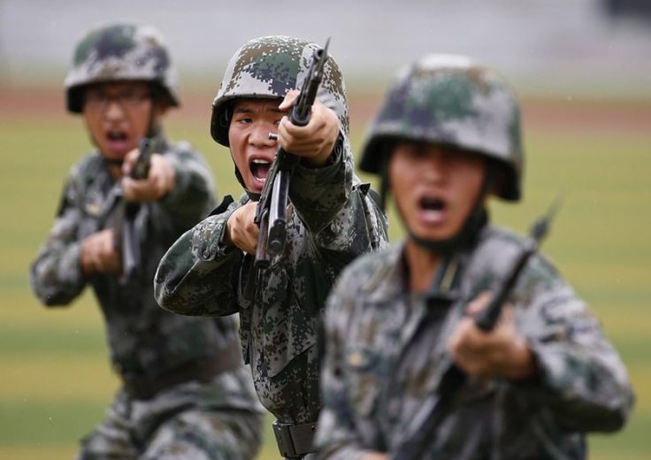 People's Liberation Army (PLA) soldiers shout as they hold guns and practise in a drill during a organized media tour at a PLA engineering school in Beijing