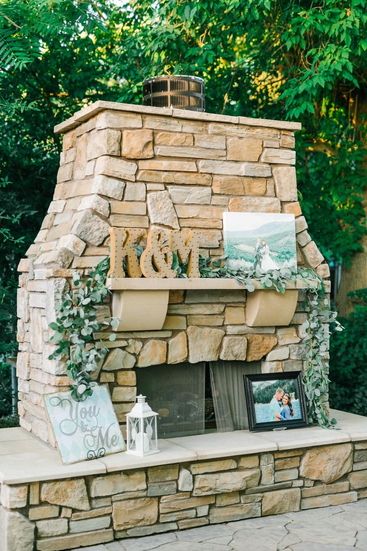 Perfect, cozy fireplace for an outdoor wedding. Eucalyptus garland. Fireplace mantle decor.