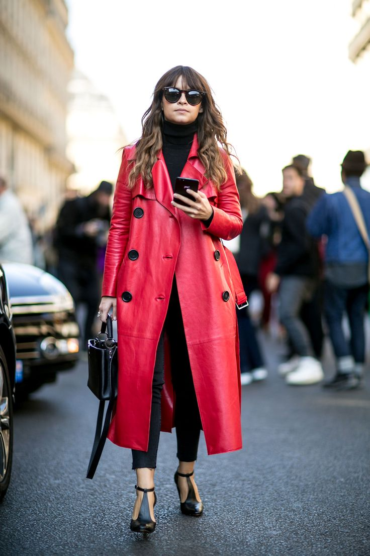 A double-breasted red coat layered over black denim jeans and a turtleneck sweater
