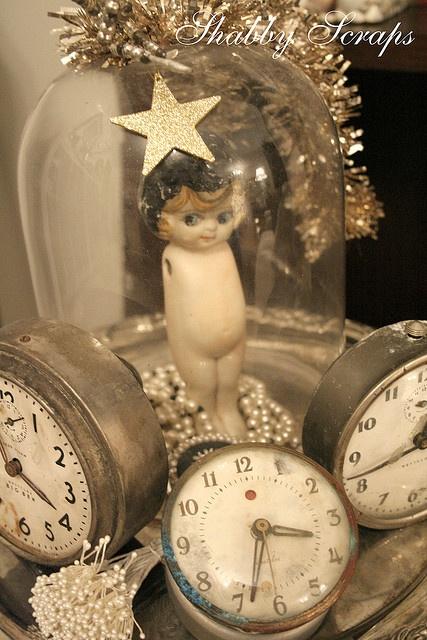 Kewpie in cloche surrounded by vintage clocks.