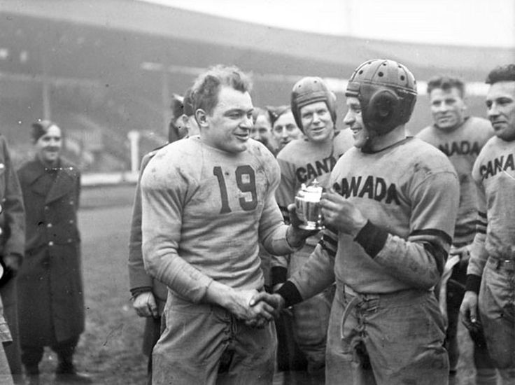Team captains shake hands after a Canada-United States American football game at White City Stadium, February 14 1944. Originally The Great Stadium, it was built in White City, London, for the 1908 Summer Olympics and is often seen as the precursor to the modern seater stadium and noted for hosting the finish of the first modern distance marathon. It also hosted greyhound racing, speedway and a match at the 1966 World Cup, before the stadium was demolished in 1985.