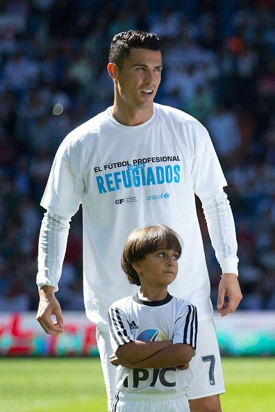 Ronaldo and the rest of the Real Madrid squad were all wearing T-shirts expressing their support for the thousands of refugees that have fled their war-torn countries and headed to Europe. | Cristiano Ronaldo Brings Syrian Refugee Boy Onto Soccer Field - BuzzFeed News