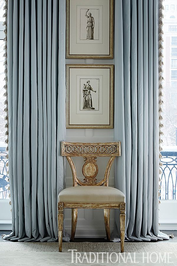 Elegant blue draperies frame an pretty side chair and stacked artwork. - Photo: Werner Straube / Design: Gail Plechaty