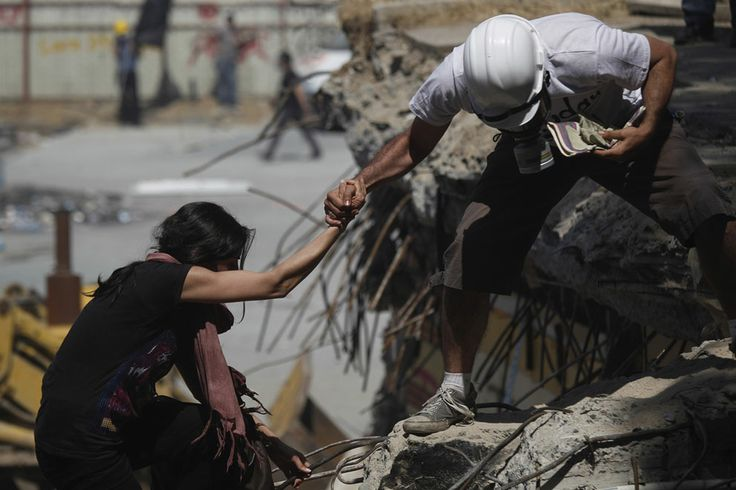 A protester helps another to climb in Gezi Park during clashes on June 11, 2013