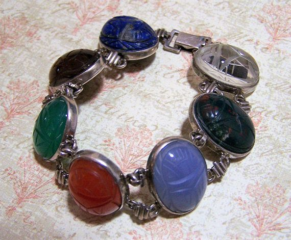 Egyptian Revival sterling silver scarab bracelet, sideways orientation Scarabs include lapis, tigers eye, chalcedony, carnelian, chrysoprase, bloodstone, quartz WRE is the WE Richards company Signed on back of fold over clasp WRE Sterling 7 1/4 inches long, 7/8 inch wide Scarabs are carved on both sides Each scarab is 15 x 20 mm All soldered connectors Good vintage condition, little to no wear to the back International buyers welcome, overcharges are always refunded I specialize in ...