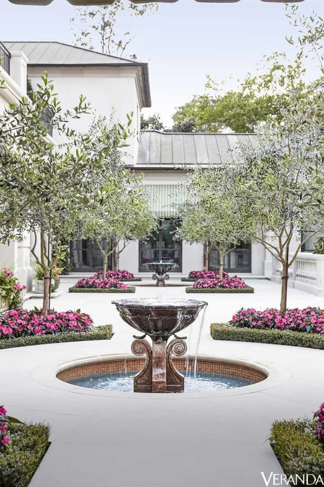 The courtyard is planted with olive trees and beds of impatiens; flooring, Lueders Limestone.   - Veranda.com