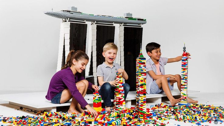 Three children build with colourful LEGO bricks in front of a large scale model of Marina Bay Sands resort
